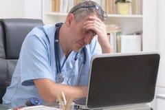 劳累过度的医生在他的办公室 免版税库存图片