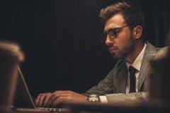 劳累过度的年轻商人与膝上型计算机一起使用在夜间 免版税库存图片
