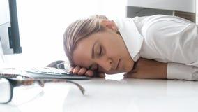 劳累过度的年轻女实业家特写镜头照片睡着了在工作地点 库存图片