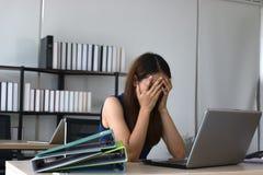 劳累过度的疲乏的年轻亚裔女商人用在面孔感觉消沉的手在办公室工作场所  库存图片