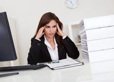 劳累过度的女实业家在办公室 免版税库存图片