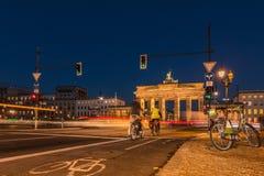 勃兰登堡门在与骑自行车者和ebike的晚上 库存图片