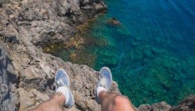 年轻勇敢的人坐在海洋上的高峭壁 库存照片