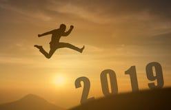 2019勇敢的人成功的概念,跳过太阳的剪影人在山的空白之间到2019个新年,感觉象wi 免版税库存图片