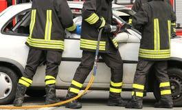 勇敢的消防队员解除在公路事故以后被伤害的  免版税库存照片