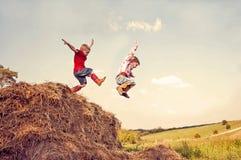 勇敢,无忧无虑的男孩跳干草 免版税库存照片