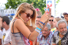 勒芒,法国- 2014年6月13日:美丽的女孩在人围拢的智能手机做自画象 库存图片