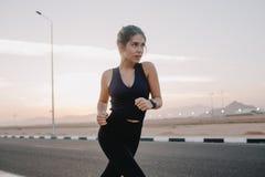 勤勉有动机的惊人的年轻女人的愉快的晴朗的早晨片刻运行在路的运动服的在清早 库存图片