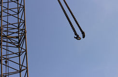 勾子和景气举的机械在一个建造场所天空背景的 免版税库存照片