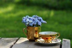 勿忘草花束在金黄杯子和金黄茶杯的 免版税库存图片