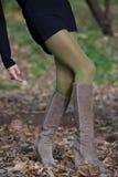 匀称女性腿在秋叶 免版税库存照片