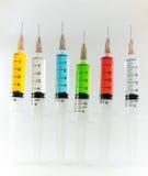 包含多色解答有白色背景的塑料医疗注射器 免版税库存照片