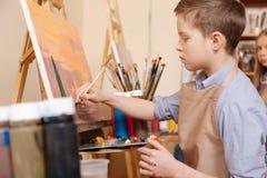 包含的年轻男孩有教训在艺术学校 库存照片