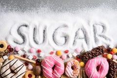 包含糖的食物 甜油炸圈饼、蛋糕和糖果的混合与糖传播和书面文本在不健康的营养方面,巧克力 免版税库存照片