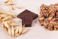 包含铁和纤维,健康快餐概念的燕麦、剥落、格兰诺拉麦片和巧克力的耳朵 免版税库存照片