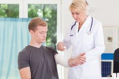 包扎患者的上部肢体医生 免版税图库摄影