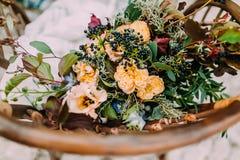 包括不同的花的美丽的婚礼花束说谎在一把老棕色椅子 库存图片