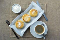 包括与酸性稀奶油和咖啡的早餐薄煎饼 图库摄影