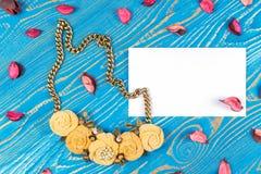 包括五朵花和一张贺卡与祝贺的手工制造项链蓝色木背景 库存图片