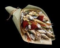 包括干鱼、芯片、开心果和快餐在黑背景的花束作为礼物对她的丈夫 免版税库存照片