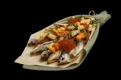 包括干鱼,薄脆饼干,干乌贼的独特的可食的花束隔绝在黑背景 免版税库存图片