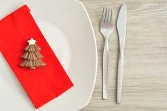 包括板材的圣诞节的一个简单的餐位餐具,叉子、刀子、红色餐巾和巧克力塑造圣诞树 库存图片