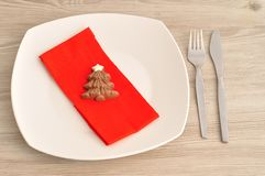 包括板材的圣诞节的一个简单的餐位餐具,叉子、刀子、红色餐巾和巧克力塑造圣诞树 免版税库存图片