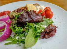 包括油鱼和夏天菜的新作冷的沙拉看见在一张木桌上 库存图片