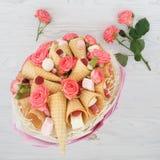 包括玫瑰、奶蛋烘饼锥体、甜点和蛋白软糖的花原始的花束在轻的木背景 库存照片