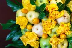 包括苹果、金桔和美丽的玫瑰的水果的黄色花束作为礼物 库存照片
