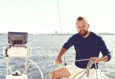 包缠在游艇的英俊,有胡子的人一条绳索 旅行, vaca 免版税库存图片