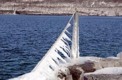 包缠垂悬岩石码头的被鞭打的冰柱 库存照片