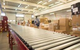 包装分布的包裹的传送带在storehous的敦豪航空货运公司中 免版税库存照片