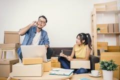 包装和移动他们的房子,网上营销包装和交付的年轻夫妇, 免版税库存图片
