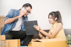 包装和移动他们的房子,网上营销包装和交付的年轻夫妇, 库存图片