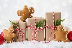 包装圣诞节礼物 在牛皮纸包裹的三个圣诞礼物箱子栓与红色和白色串,姜饼人 免版税图库摄影