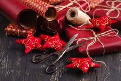 包装在葡萄酒卷轴式记录纸的圣诞节礼物在老木书桌上 免版税库存图片