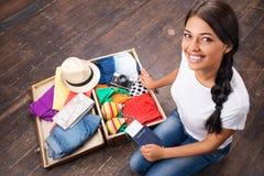包装她的手提箱的愉快的女孩 免版税库存图片
