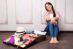 包装她的手提箱的美丽的女孩 免版税库存图片