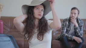 包装手提箱的逗人喜爱的俏丽的妇女在旅行前,尝试在帽子的夫人在手提箱然后投入了它 愤概有胡子 股票录像