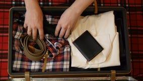 包装旅行的人手手提箱 r 法绒衬衣、牛仔裤、电剃刀、威士忌酒和其他辅助部件为 影视素材