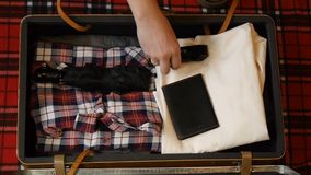 包装旅行的人手手提箱 r 法绒衬衣、牛仔裤、电剃刀和其他辅助部件行家的 股票录像