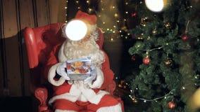 包装礼物盒的圣诞老人坐在椅子在圣诞树附近 影视素材