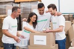 包装食物捐赠箱子的志愿队 免版税库存照片