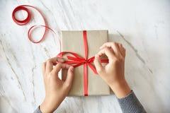 包裹一个棕色当前箱子的女性手 免版税库存照片