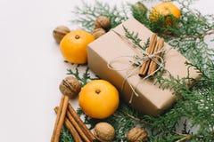 包裹与工艺纸、串、蜜桔和自然冷杉分支的被定调子的instagram图象土气eco圣诞节礼物在白色b 库存照片