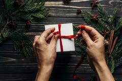 包裹与红色丝带的手圣诞节礼物在时髦的木头 免版税库存图片