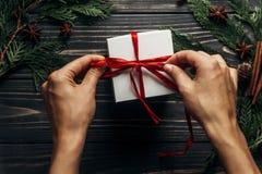 包裹与红色丝带的手圣诞节礼物在时髦的木头 库存图片