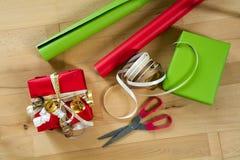 包裹与红色和绿皮书、丝带和剪刀的礼物  免版税库存照片