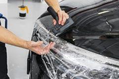 包裹专家的汽车把乙烯基箔或影片放在汽车上 在汽车的保护胶卷 适用于保护胶卷汽车与 免版税库存照片